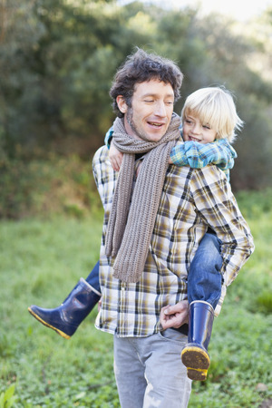 Father carrying son piggyback outdoors Stock Photo
