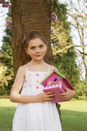 Girl holding birdhouse in backyard