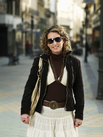 Young woman wearing sunglasses standing in street, smiling Stock Photo