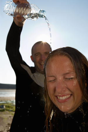 socialise: Laughing man pouring water over womans head.
