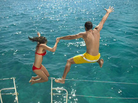 Couple jumping into sea from boat, rear view