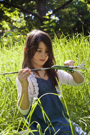 Girl painting model airplane outdoors