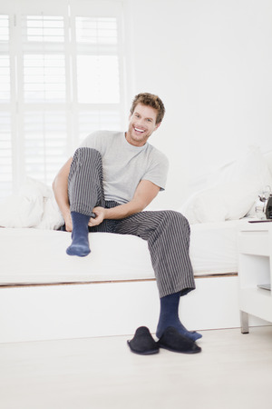 Man putting socks on in bed Stock Photo