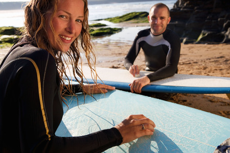 socialise: Couple waxing their surfboards smiling.