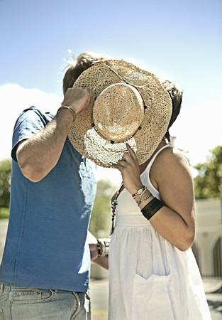 Couple kissing behind sunhat in park