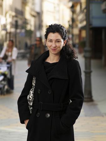 Woman wearing black coat standing in street, smiling, portrait