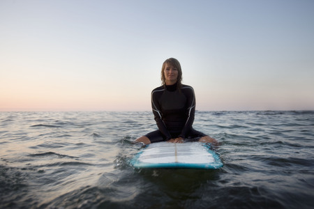 Woman sitting on surfboard in the water smiling.