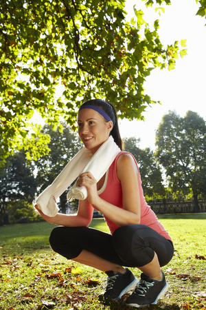 Runner wearing towel in park Stock Photo