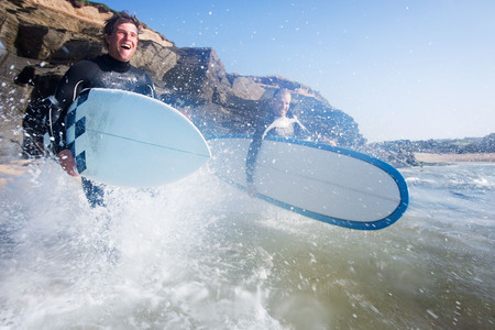 socialise: Two men running into the water with surfboards smiling.