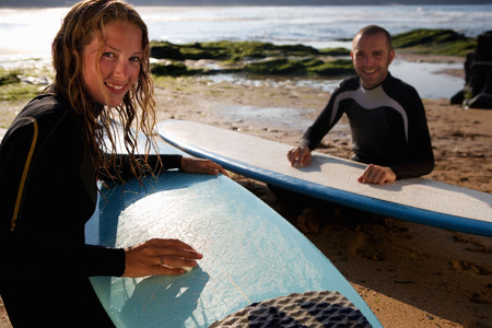 waxes: Couple waxing their surfboards smiling.