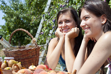 Smiling women picnicking in orchard Stock Photo