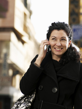 Woman standing in street using mobile phone, smiling