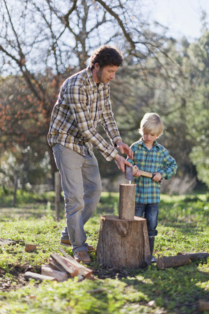 trusted: Father teaching son to chop wood