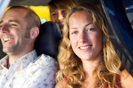 Three people in a van smiling. Stock Photo
