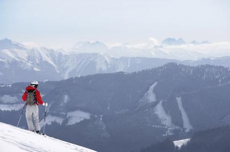 Österreich, Saalbach, männlicher Skifahrer, der auf Steigung, Berge in der Ferne steht