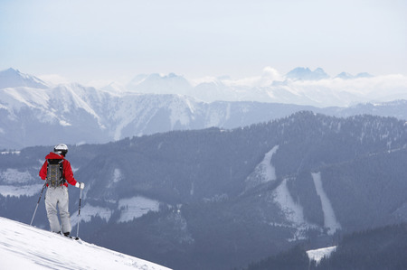 Austria, Saalbach, male skier standing on slope, mountains in distance