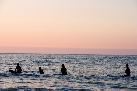Four people sitting on surfboards