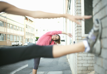 Runners stretching against wall