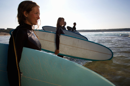 Four people standing with surfboards in the water smiling.