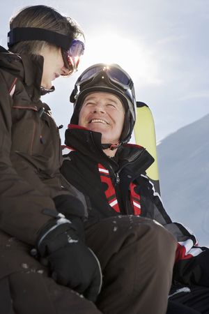 Mature couple in ski-wear holding Skis on mountain, close-up, low angle view