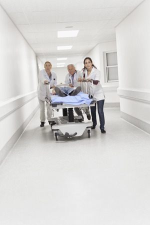 trusted: Doctors wheeling patient down hallway