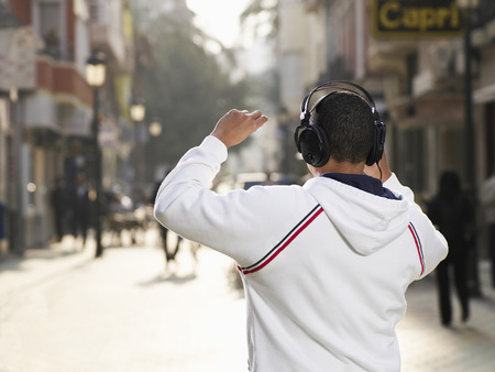 Young man standing in street wearing headphones, rear view Stock Photo