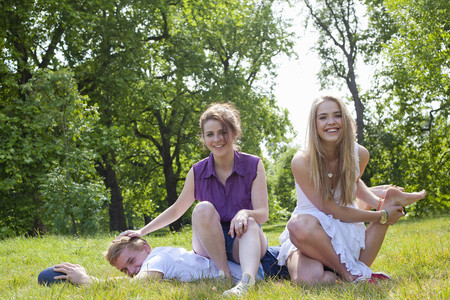 Teenagers playing in grass in park