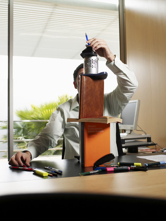 Businessman making tower of stationary equipment on desk Stock Photo