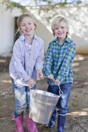 Children carrying heavy pail outdoors