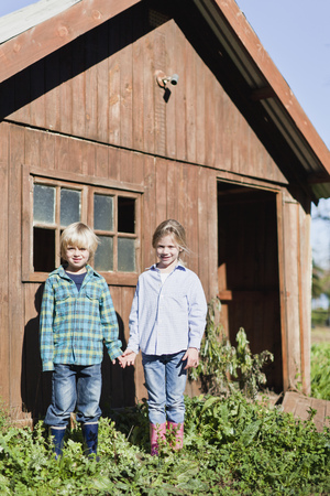 Children holding hands outside shed Stock Photo