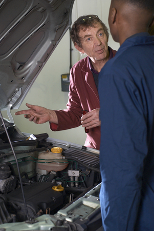 Teacher helping students with car engine Stok Fotoğraf