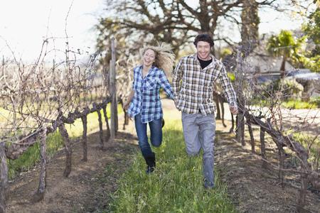 Smiling couple running in vineyard