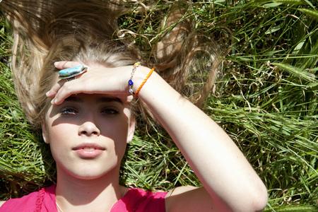 Teenage girl lying in tall grass Stock Photo