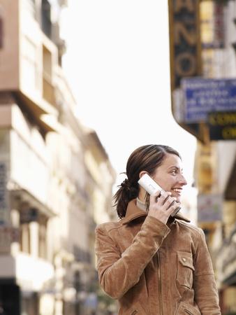 Jonge vrouw die zich in straat bevindt die mobiele telefoon, het glimlachen gebruikt Stockfoto