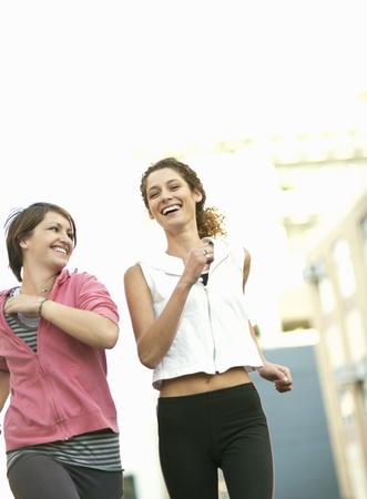 Smiling women jogging together