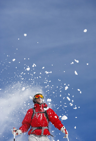 Snow spraying over male skier, low angle view