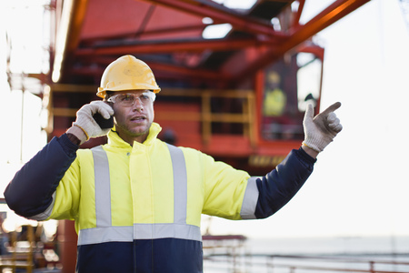 Worker using walkie talkie on oil rig Stock fotó