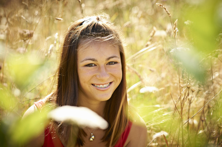 Teenage girl smiling in tall grass Stock Photo