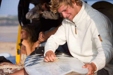 Man waxing surfboard with couple smiling in background.