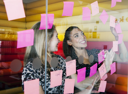 Businesswomen sticking notes on window