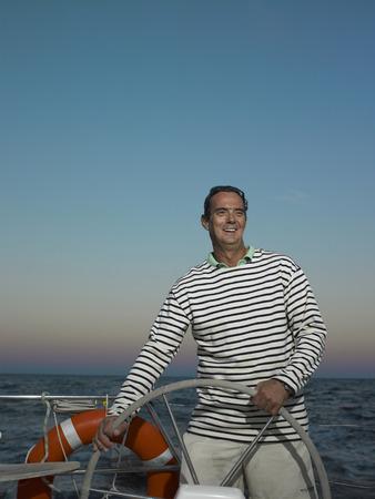 successfulness: Mature man steering yacht, smiling Stock Photo