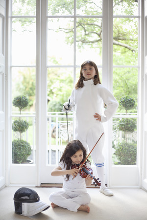 Two girls with violin and fencing gear Stock Photo