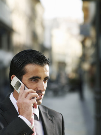 Young businessman using mobile phone in street, close-up Stockfoto
