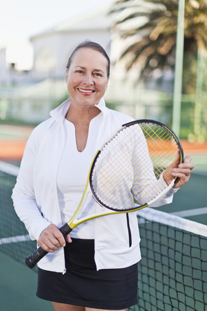Older woman with tennis racket on court Stock Photo