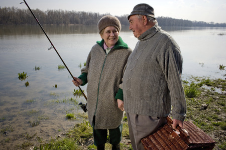 Senior couple carrying picnic basket and fishing rod by river, smiling Stock Photo