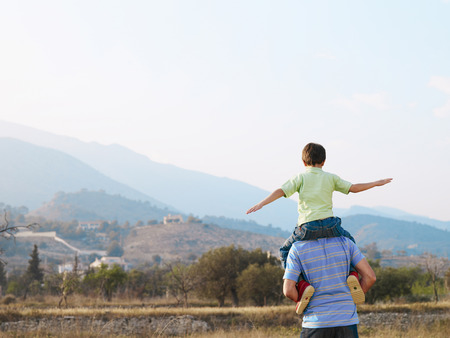 Father carrying son (6-8) on shoulders in field, rear view