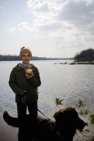 Boy (12-14) walking dog by river, holding apple, smiling, portrait Stock Photo