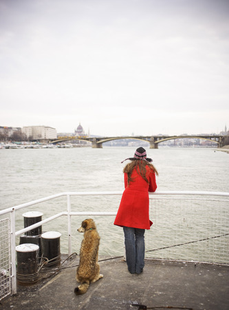 Hungary, River Danube, young woman on jetty with dog, rear view