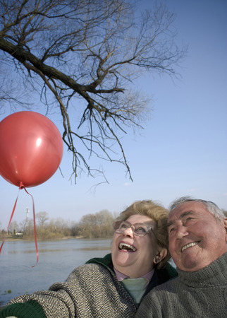 Senior couple by river holding red balloon, heads together, smiling
