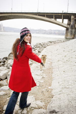 Young woman walking dog by river, looking over shoulder, smiling Stock Photo